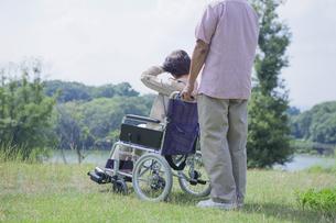車椅子で散歩をする夫婦の写真素材 [FYI04255381]
