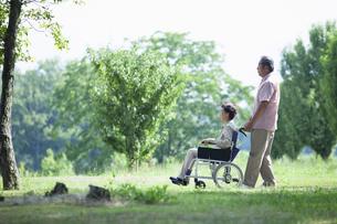 車椅子で散歩をする夫婦の写真素材 [FYI04255420]