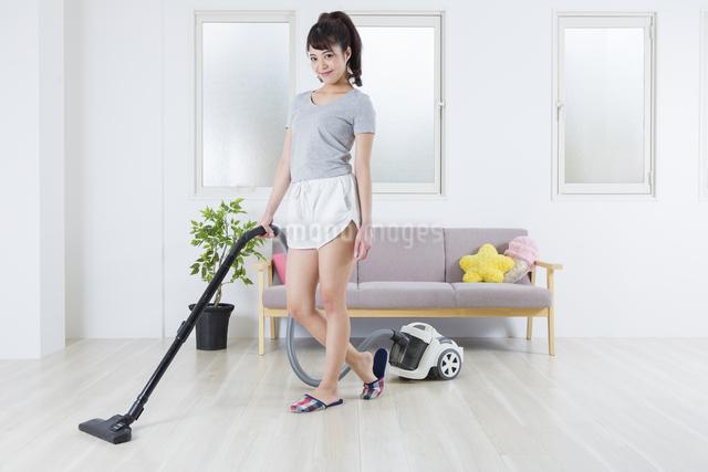 掃除機をかける女性の写真素材 [FYI04257448]