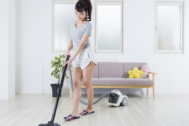 掃除機をかける女性の写真素材 [FYI04257451]