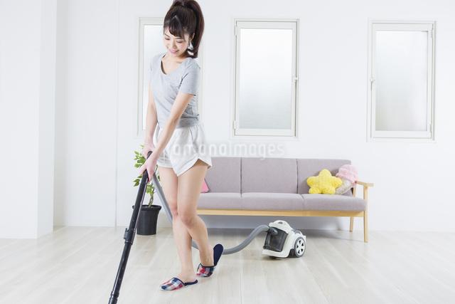 掃除機をかける女性の写真素材 [FYI04257452]