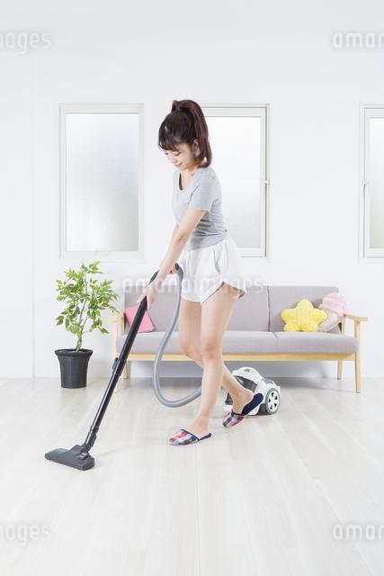 掃除機をかける女性の写真素材 [FYI04257453]