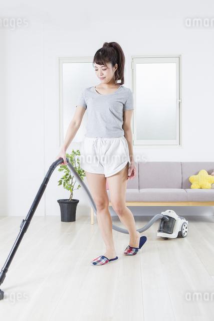 掃除機をかける女性の写真素材 [FYI04257454]