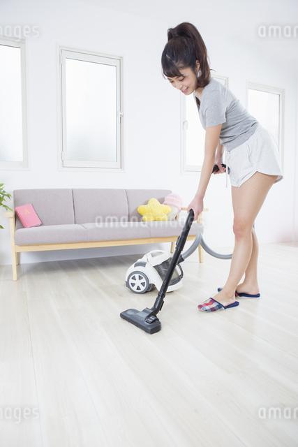 掃除機をかける女性の写真素材 [FYI04257457]