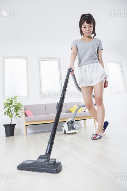 掃除機をかける女性の写真素材 [FYI04257459]