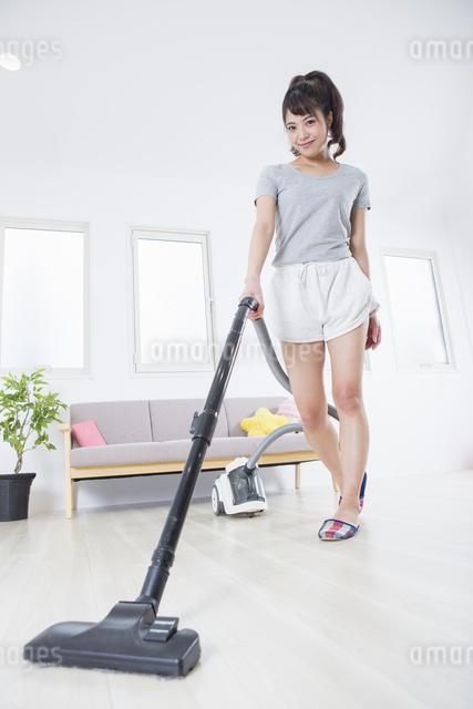 掃除機をかける女性の写真素材 [FYI04257460]