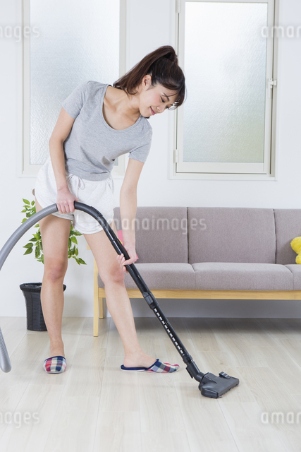 掃除機をかける女性の写真素材 [FYI04257465]
