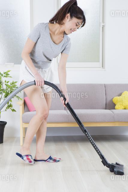 掃除機をかける女性の写真素材 [FYI04257469]