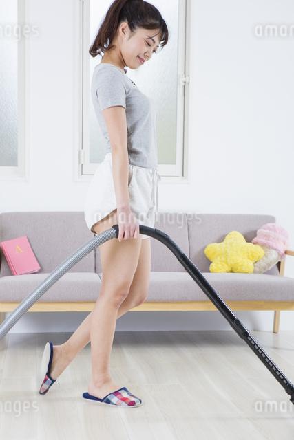 掃除機をかける女性の写真素材 [FYI04257471]