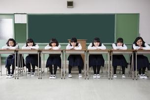 一列に机を並べて座る女子生徒の写真素材 [FYI04257954]
