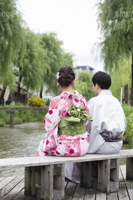 河原のベンチで座るカップルの写真素材 [FYI04258409]
