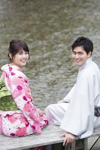 河原のベンチで座るカップルの写真素材 [FYI04258414]