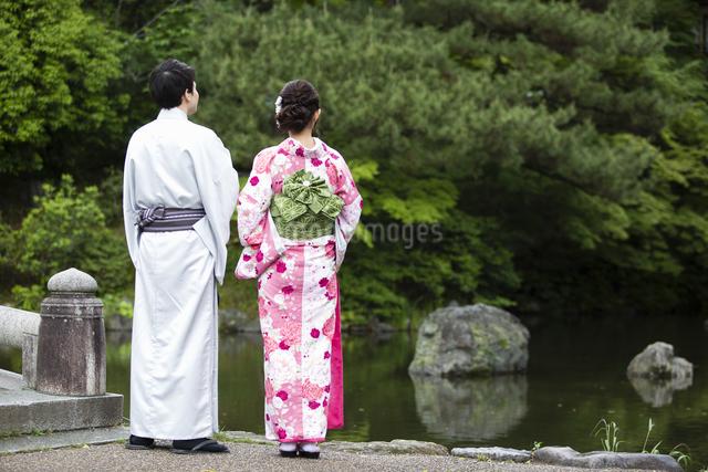 池のほとりで立つカップルの写真素材 [FYI04258467]