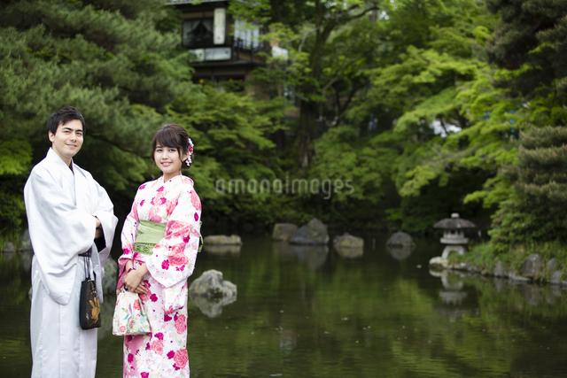 池のほとりで立つカップルの写真素材 [FYI04258472]