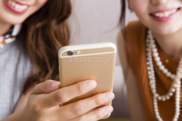 スマホを操作する女性たちの写真素材 [FYI04259654]