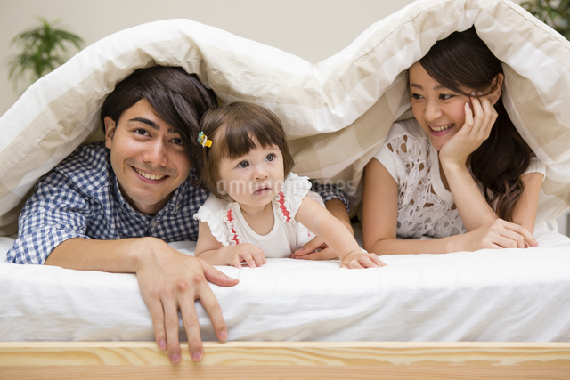布団の中に潜る家族の写真素材 [FYI04260012]