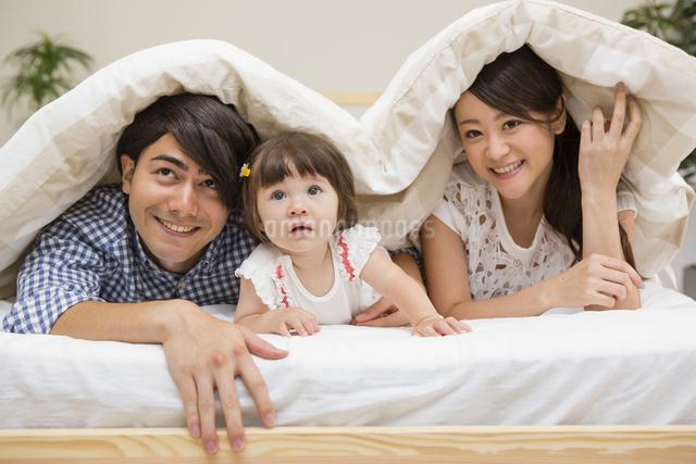 布団の中に潜る家族の写真素材 [FYI04260013]