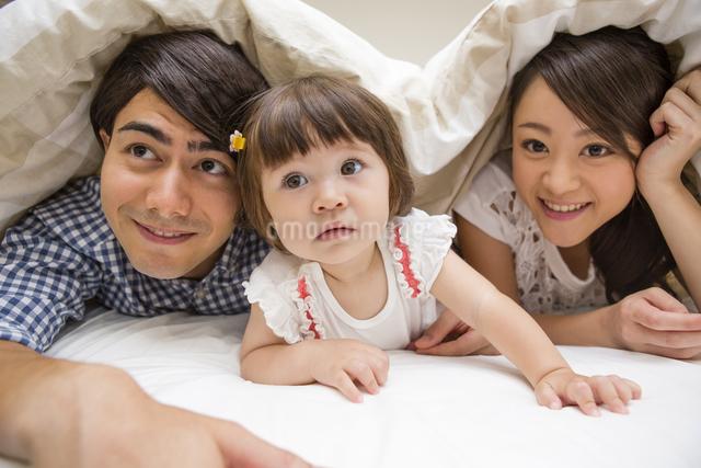 布団の中に潜る家族の写真素材 [FYI04260014]