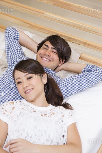 ベッドに寝転がる男女の写真素材 [FYI04260021]