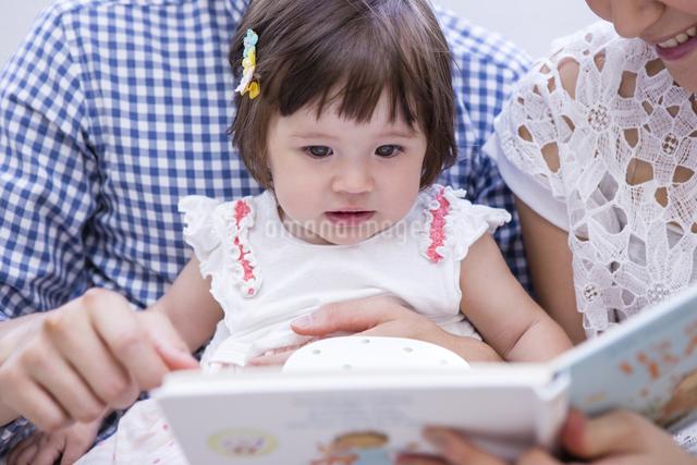 ソファで絵本を読む家族の写真素材 [FYI04260103]