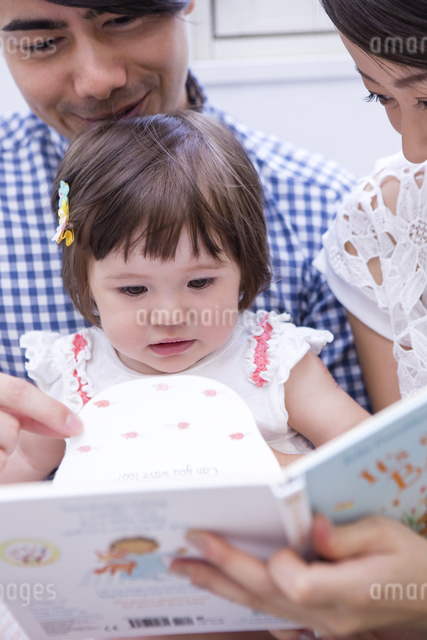 ソファで絵本を読む家族の写真素材 [FYI04260104]