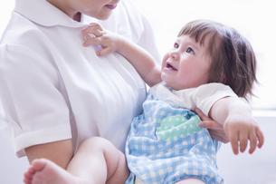 子供を抱っこする看護士の写真素材 [FYI04260281]