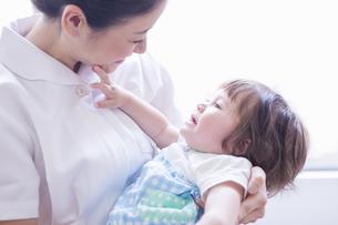 子供を抱っこする看護士の写真素材 [FYI04260282]