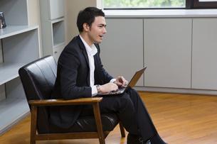 座りながら話すビジネスマンの写真素材 [FYI04262276]