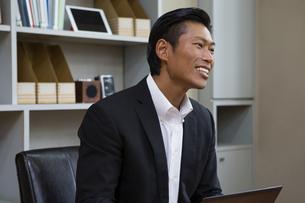 座りながら話すビジネスマンの写真素材 [FYI04262309]