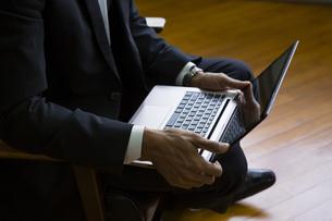 座ってパソコンをするビジネスマンの写真素材 [FYI04262314]