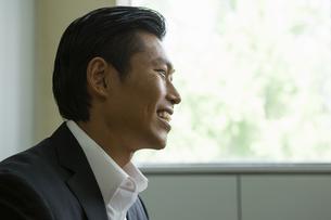 座りながら話すビジネスマンの写真素材 [FYI04262315]