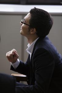 座りながら話を聞くビジネスマンの写真素材 [FYI04262411]