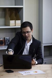 電話しながらパソコンをするビジネスパーソンの写真素材 [FYI04262569]
