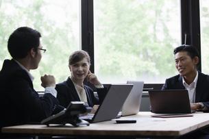 パソコンをしながら談笑するビジネスパーソンの写真素材 [FYI04262586]