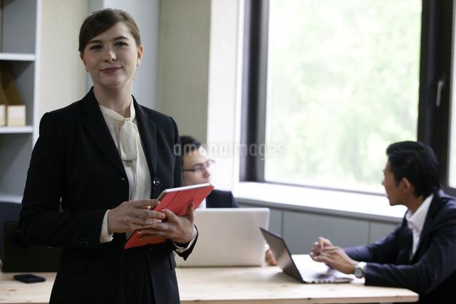 パソコンをしながら談笑するビジネスパーソンの写真素材 [FYI04262625]