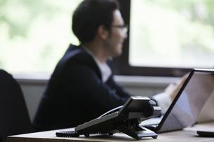 パソコンをしながら談笑するビジネスパーソンの写真素材 [FYI04262653]