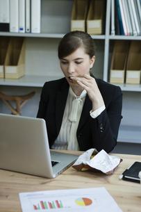 仕事をしながら食事をとるビジネスウーマンの写真素材 [FYI04262695]