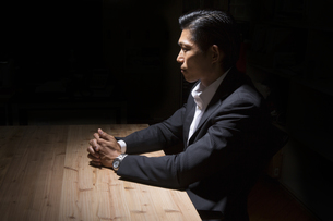 暗闇の中で手を組むビジネスマンの写真素材 [FYI04262779]