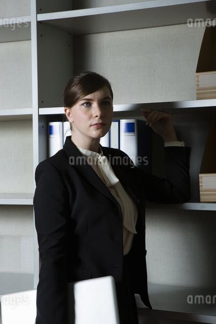 本棚の前でたたずむビジネスウーマンの写真素材 [FYI04262803]