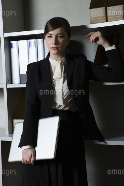 本棚の前でたたずむビジネスウーマンの写真素材 [FYI04262804]