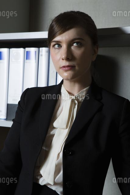 本棚の前でたたずむビジネスウーマンの写真素材 [FYI04262813]