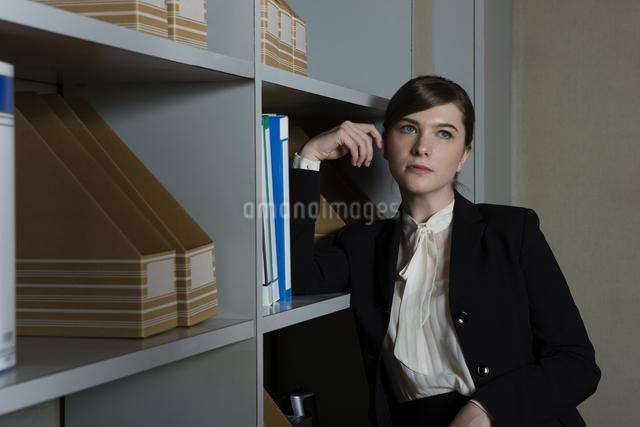 本棚にもたれるビジネスウーマンの写真素材 [FYI04262814]