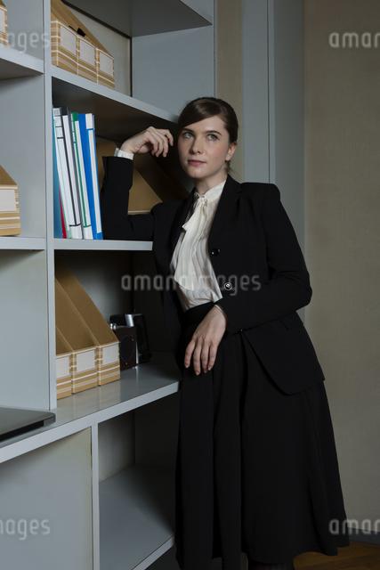 本棚にもたれるビジネスウーマンの写真素材 [FYI04262815]