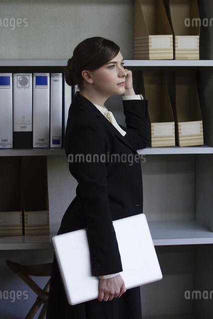 本棚にもたれるビジネスウーマンの写真素材 [FYI04262823]