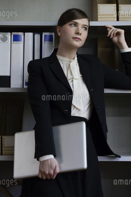 本棚にもたれるビジネスウーマンの写真素材 [FYI04262826]