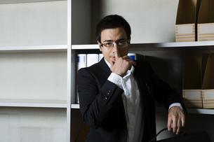本棚の前で眼鏡を直すビジネスマンの写真素材 [FYI04262839]