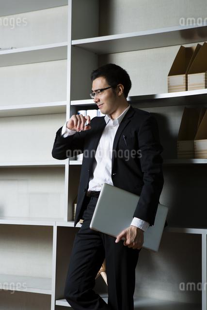 本棚にもたれるビジネスマンの写真素材 [FYI04262842]