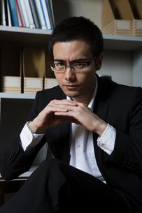 本棚の前の椅子に座るビジネスマンの写真素材 [FYI04262849]