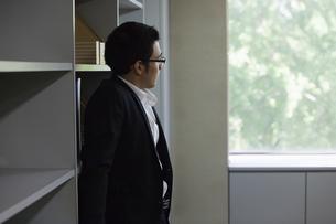 本棚にもたれるビジネスマンの写真素材 [FYI04262859]