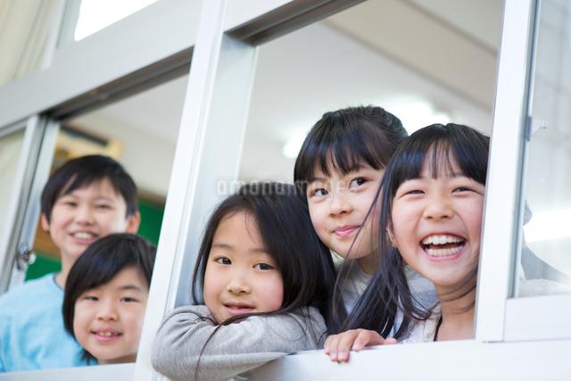 窓から顔を出す小学生の写真素材 [FYI04263963]